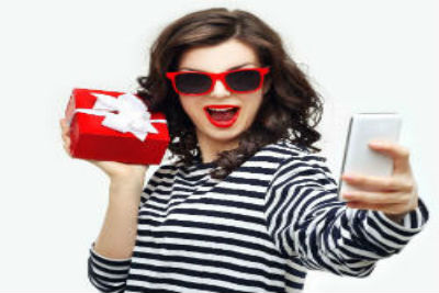 Girl Holding Gift Taking A Selfie Front Cover Holiday Gift Ideas in Lancaster for the Whole Family